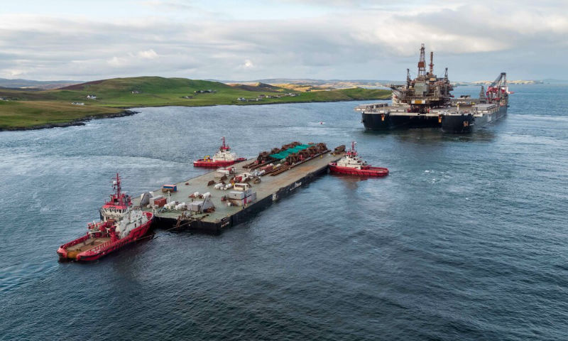 The barge, 'Iron Lady' is in the foreground, with the 'Pioneering Spirit' beyond (Courtesy Lerwick Port Authority/Rory Gillies/Shetland Flyer Aerial Media)