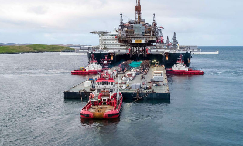 The barge, 'Iron Lady', is manoeuvered into position between the hulls of 'Pioneering Spirit', ready to receive the platform topsides (Courtesy Lerwick Port Authority/Rory Gillies/Shetland Flyer Aerial Media)